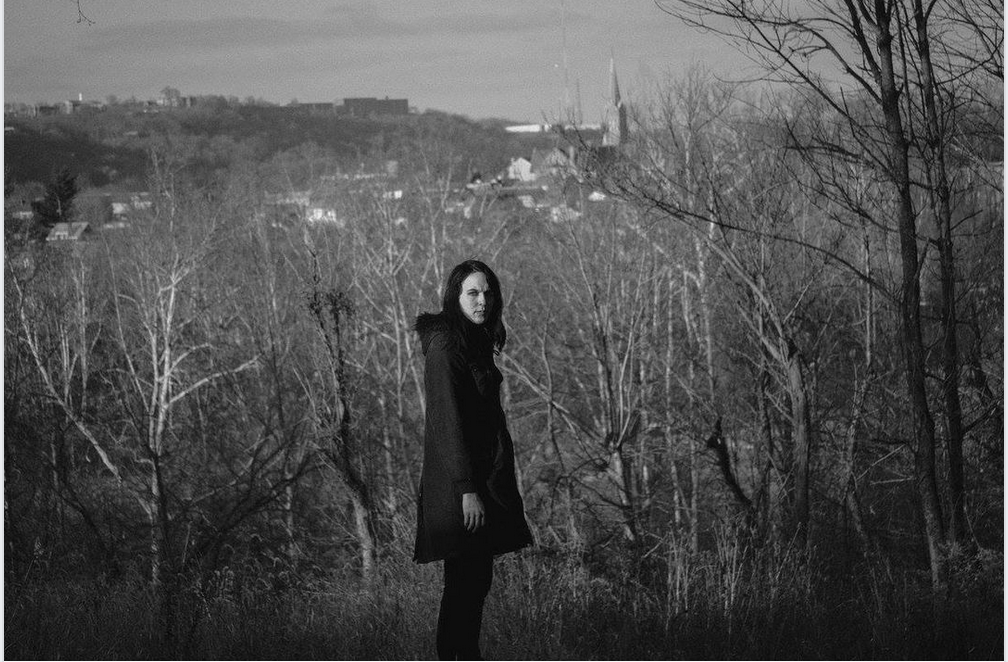A black and white photograph shows Stacy Jane Grover looks over her shoulder at the camera. Behind her is a wooded mountainside. Behind her in the distance is a church steeple and some buildings.